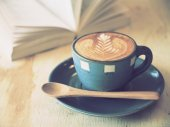 Cup of coffee with book in coffee shop vintage color — Stock Photo