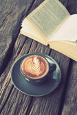 Cup of coffee latte art on the wood desk and book in vintage col — Stock Photo