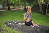 Young woman doing yoga exercises in the garden park — Stock Photo