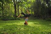 Ung kvinna gör yogaövningar i trädgården park — Stockfoto