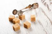 Brown sugar cubes i szczypce metal sugat — Zdjęcie stockowe