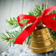 Christmas golden bell with red satin ribbon bow — Stock Photo #76135795