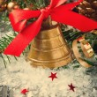 Christmas golden bell with red satin ribbon bow — Stock Photo #76135807