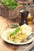 Pasta tagliatelle with pesto sauce and basil — Stock Photo