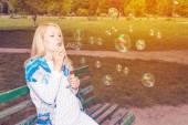 Pregnant park blowing bubbles — Stock Photo