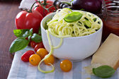 Zucchini noodles in a bowl with fresh vegetables — Stock Photo