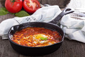 Shakshuka with tomatoes and eggs — Stock Photo