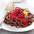 Cooked chocolate pasta with raspberry sauce — Stock Photo #70397367