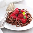 Cooked chocolate pasta with raspberry sauce — Stock Photo #70397441