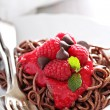 Cooked chocolate pasta with raspberry sauce — Stock Photo #75607997