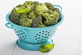 Fresh broccoli florets in blue colander — Stock Photo