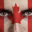 Canada, canadian flag painted on the face of young man — Stock Photo #56329669