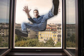 Young man falling down a window — Stock Photo