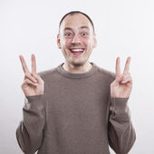 Portrait of a crazy man showing victory sign — Stock Photo