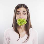 Young woman with lettace in her mouth — Stock Photo