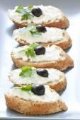 Crostini met cottage kaas, peterselie en olijven — Stockfoto