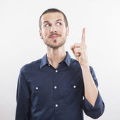 Young man pointing up, showing something — Stock Photo