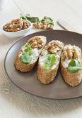 Crostini with gorgonzola cheese, arugula and walnut — Stock Photo