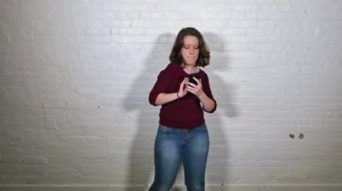 A young woman dances playfully in front of a white brick wall with her cellular telephone. — Stock Video
