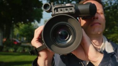 A close up shot of a cameraman focusing a shoulder-mounted camera. — Stock Video