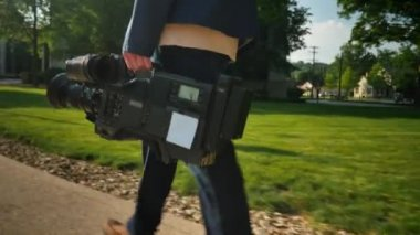 A low angle shot of a cameraman carrying his video camera to a production.  Trackable plane on camera for placement of a custom logo. — Stock Video