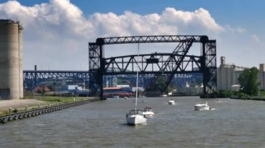 Boats travel under the many bridges on the Cuyahoga River — Stock Video