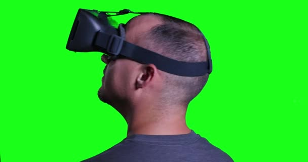 A man in a virtual reality mask looks around and manipulates his surroundings.  Green screen with optional luma matte for keying your custom background. — Vídeo de stock