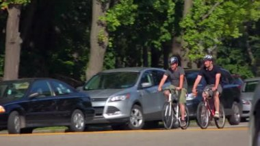 Two college-aged guys ride their bicycles on a street in Schenley Park in the Oakland area of Pittsburgh, PA.  Shot at 60fps. — Stock Video