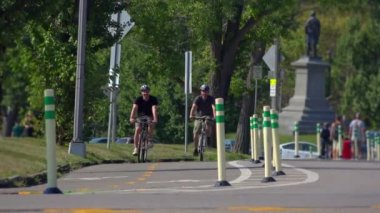 Two college-aged guys ride their bicycles in a bike lane in Schenley Park in the Oakland area of Pittsburgh, PA.  Shot at 60fps. — Stock Video