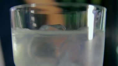 Bartender pouring a glass of ice and tonic with blue liquor — Stock Video