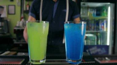 Bartender adorns two cocktails of orange slices. Dolly shot. — Stock Video