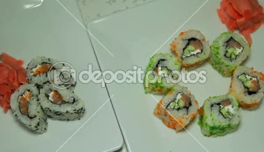 Panoraming shot of delicious sushi rolls on white plate with wasabi and ginger — Stock Video