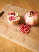 Cuted pomegranates with seeds on wooden board — Stock Photo