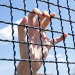 Hand grasping a metal fence — Stock Photo #73899451