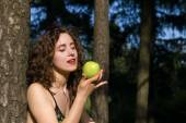 Beautiful young woman eating apple outdoors — Stock Photo