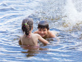 Little boy teaches his little sister to swim — Stock Photo