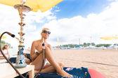 Woman with hookah on the beach in bikini — Stock Photo