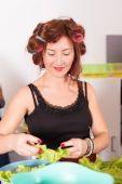 Young pretty woman housewife cooking with curlers on hair — Stock Photo