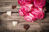 Pink fresh roses and chocolate hearts on wood — Stock Photo