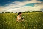 在一片草地上读书的年轻女子 — 图库照片