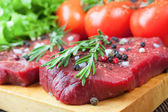 Raw beef steak with vegetables and spices — Stock Photo