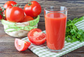 Tomato juice and fresh tomatoes on wooden table — Stock Photo