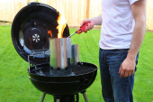 Man starting BBQ coal chimney fire with lighter — Stock Photo