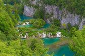 Plitvice lakes: people walking on a footbridge over water — Stock Photo