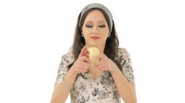 Pretty young woman making exaggerated happy expression after biting an apple — Stock Video