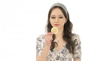Lovely young woman making facial expression after tasting a slice of sour lemon — Stock Video