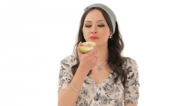 Pretty young woman biting a sour apple — Stok video