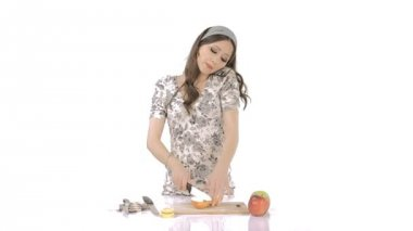 Young brunette chopping apples while speaking on mobile phone — Stock Video