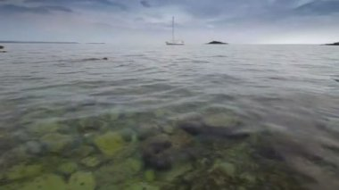 Water surface, causeway and a small island and boat in the distance. — Vídeo de stock