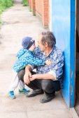 A child hugs his grandfather near the garage — Stock Photo